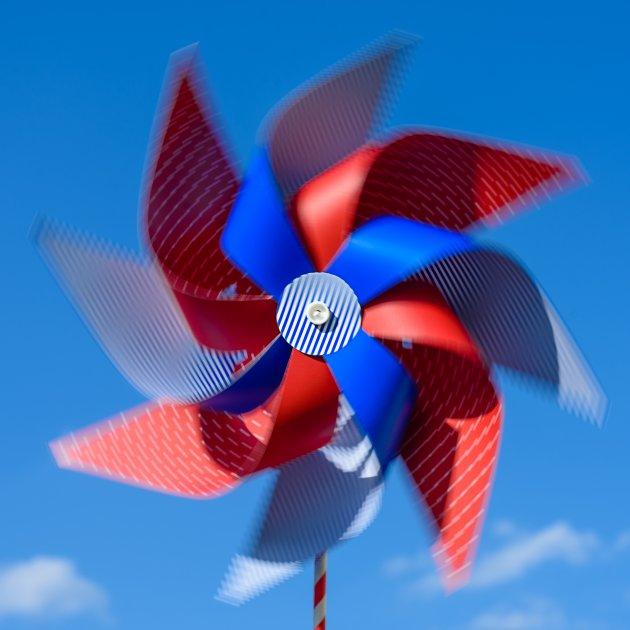 Kręcący się dziecięcy wiatraczek-zabawka, złożony z plastikowego patyczka i plastikowego mechanizmu ruchomego