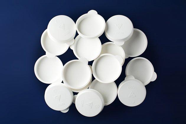 Stosik białych, plastikowych dekielków do tub o średnicy 60