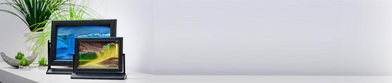 Dwa obrazki piaskowe w plastikowej ramce obrotowej na solidnych statywach