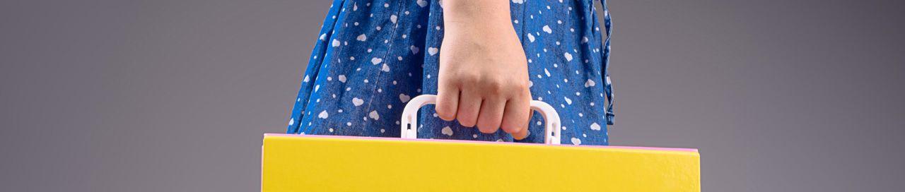 Ręka trzymająca za białą rączkę plastikową przykładową teczkę tekturową